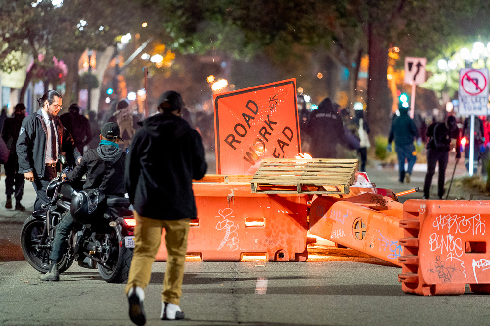 A roadblock made from construction barriers, signs, and pallets burns at Broadway Avenue and 21st Street as protesters calling for 'Justice for Jacob' march through the streets of Oakland, Calif., August 26, 2020. Jacob Blake was shot seven times in the back by police in Kenosha, Wis. — his shooting has reignited Black Lives Matter protests.