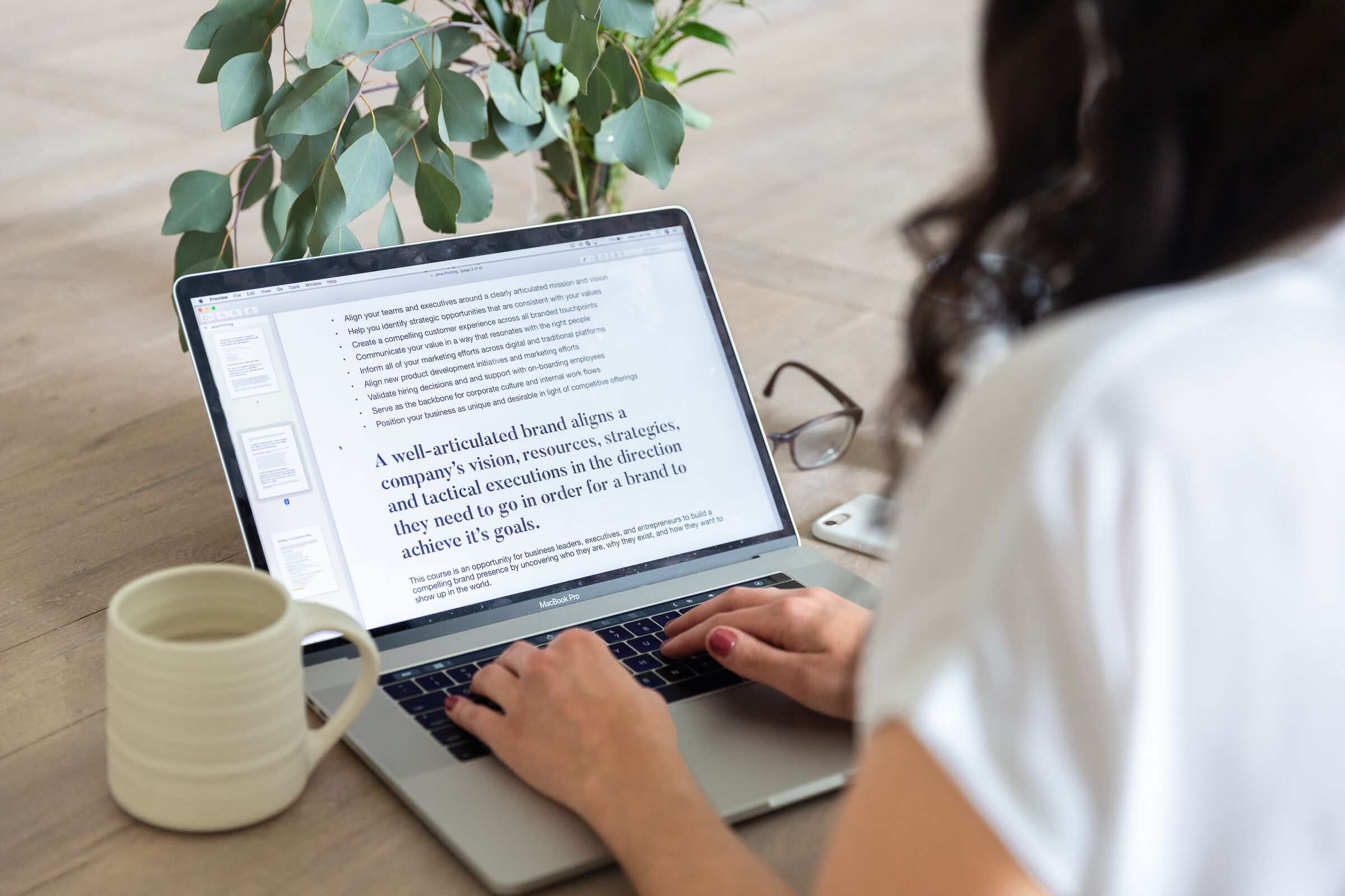 A woman working on a branding document in a trendy setting.