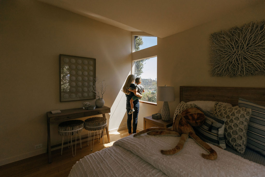 Photo of parent and child in a home looking through a window