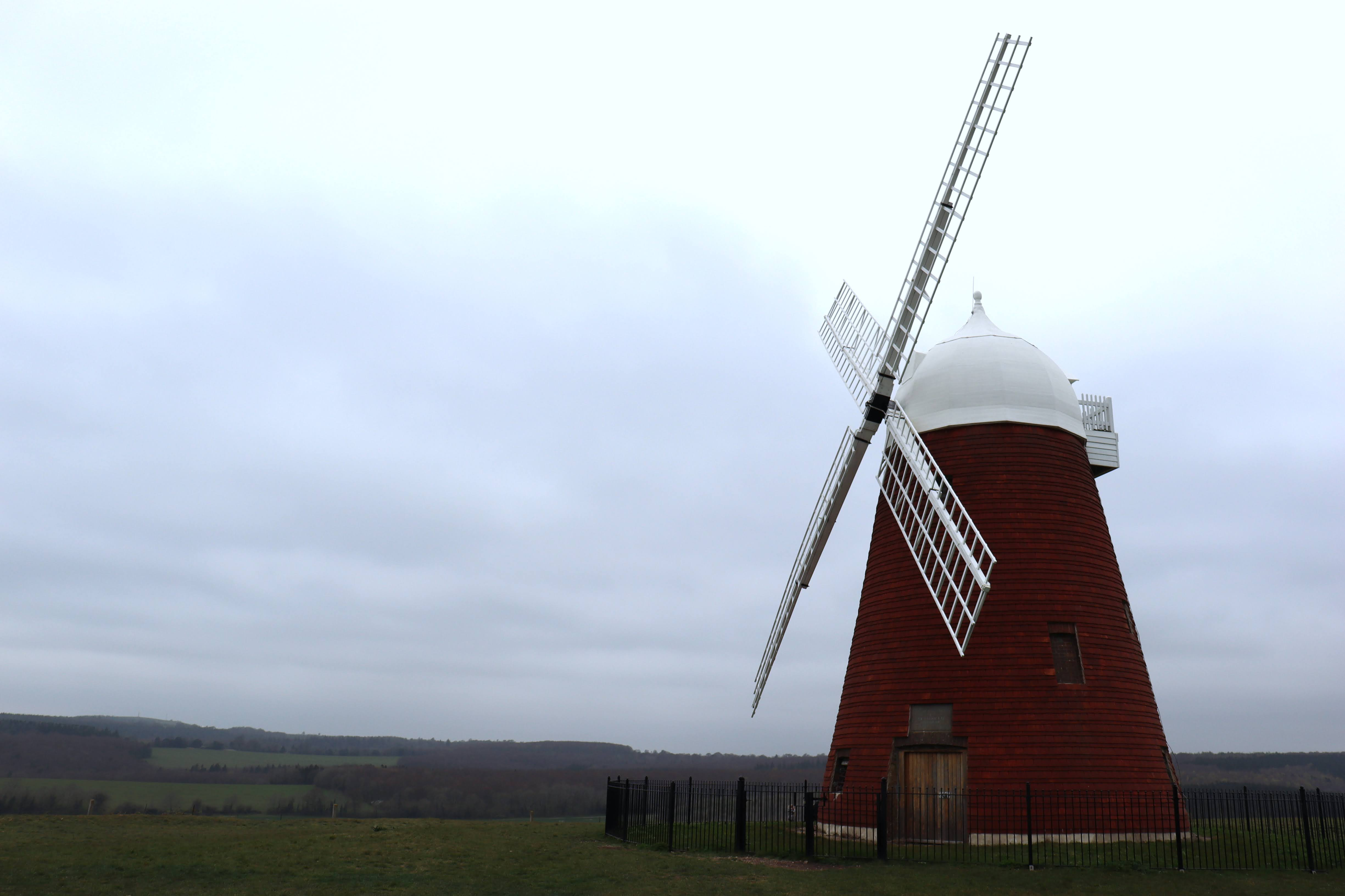 The red and white Halnaker Mill from a 45 degree angle. Surrounded by green grass and hills in the background.