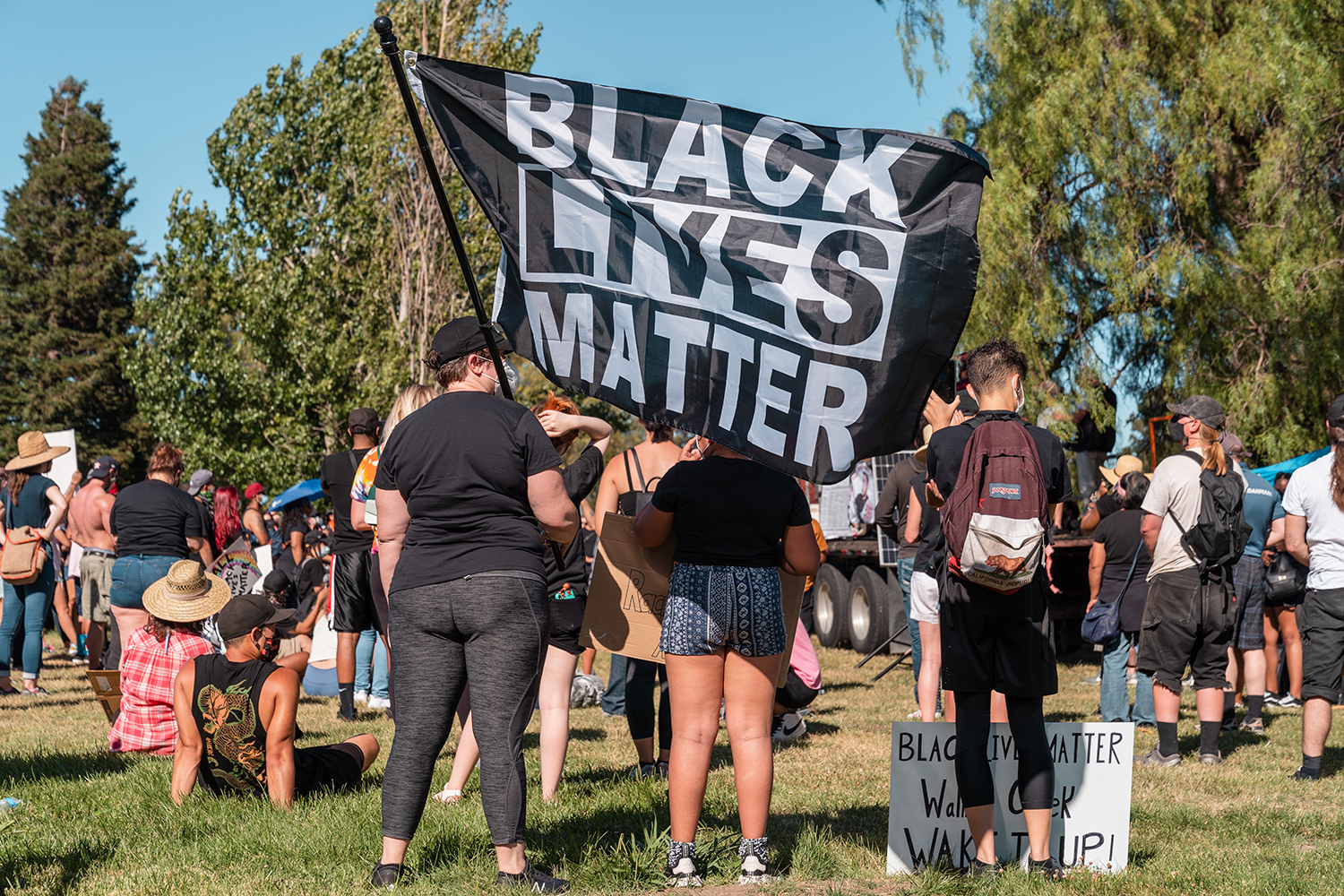 "A Black Lives Matter flag is flown as people listen to speakers at the Waterfront Park during the ""Zero Tolerance for White Supremacy"" protest in Martinez, Calif., on Sunday, July 12, 2020."