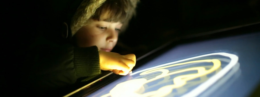 Light painting experience showcase of boy using device to paint