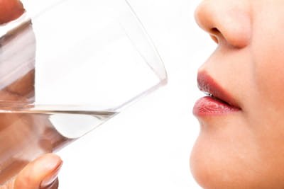A close-up photo of a woman drinking a glass of water.