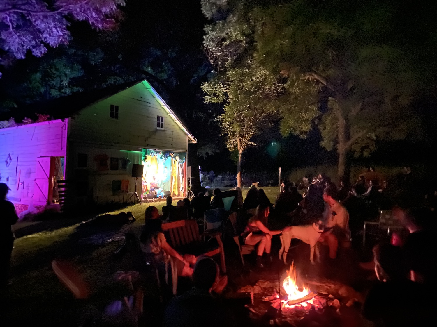 The stage lights and a campfire illuminating the grounds at a tiny music festival in Wisconsin.