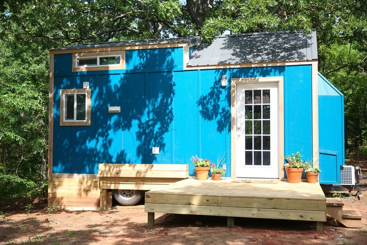Outdoor photo showing the blue tiny amenities building, with outdoor deck and a couple of windows.