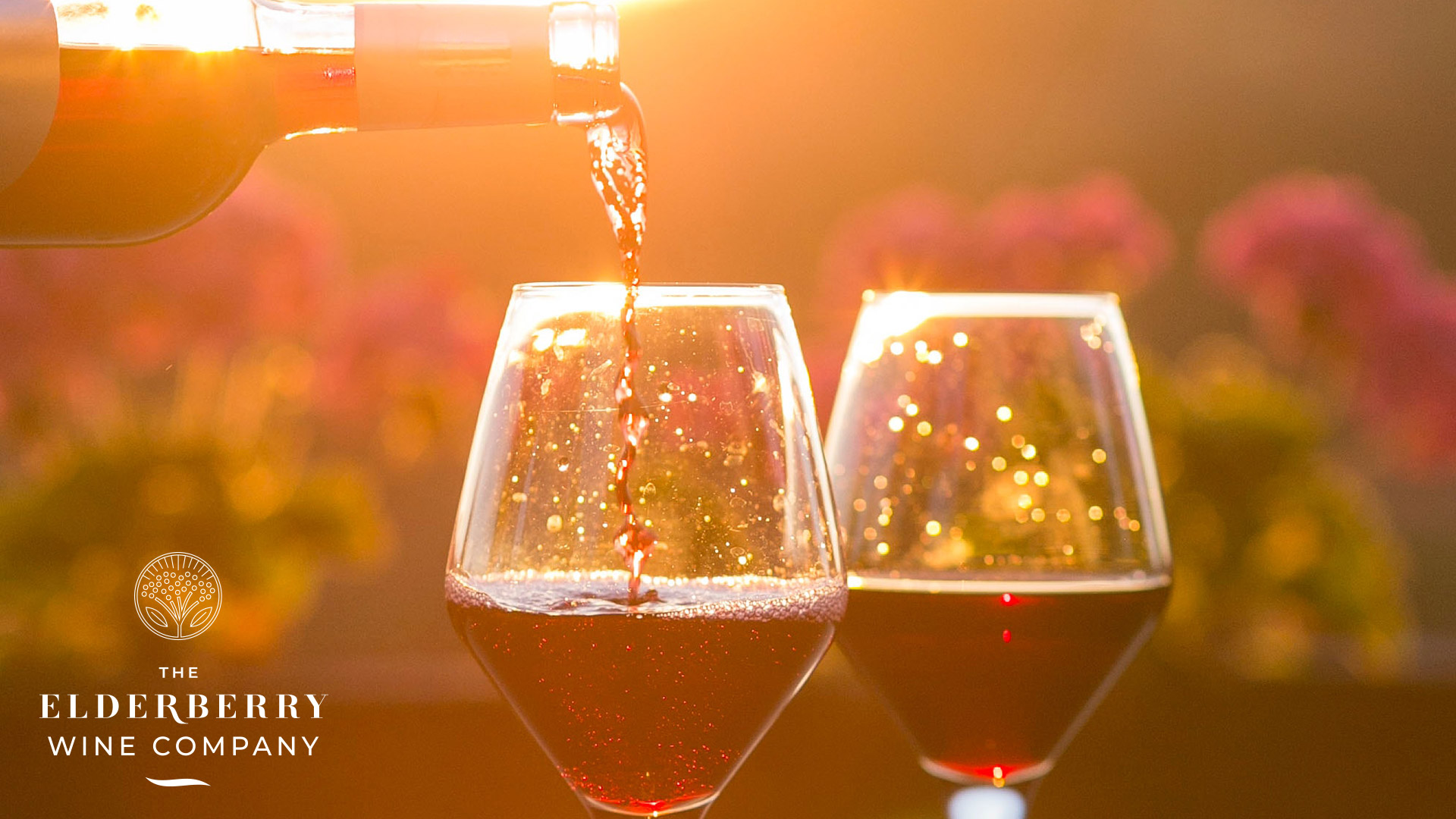 Two wine glasses being filled with elderberry wine