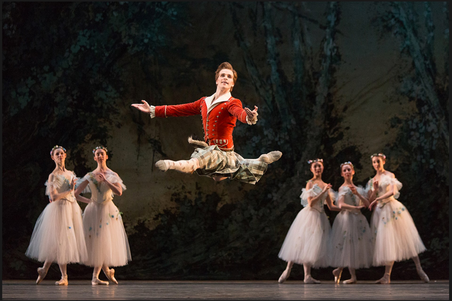 Dancer in kilt and red jacket leaps in front of chorus of ballerinas in white gauzy dresses, against painted trees backdrop.