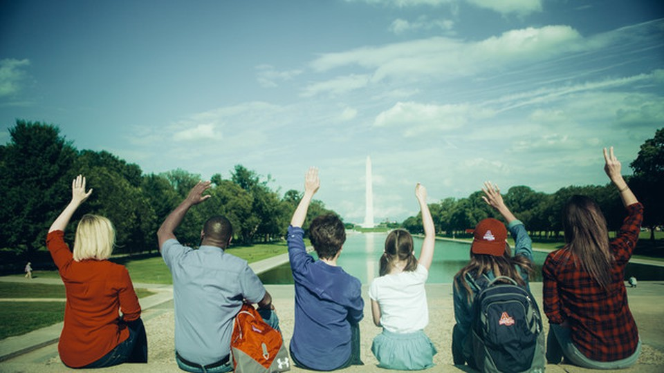 People seated in front of the Washington D.C. obelisk. They have one hand raised