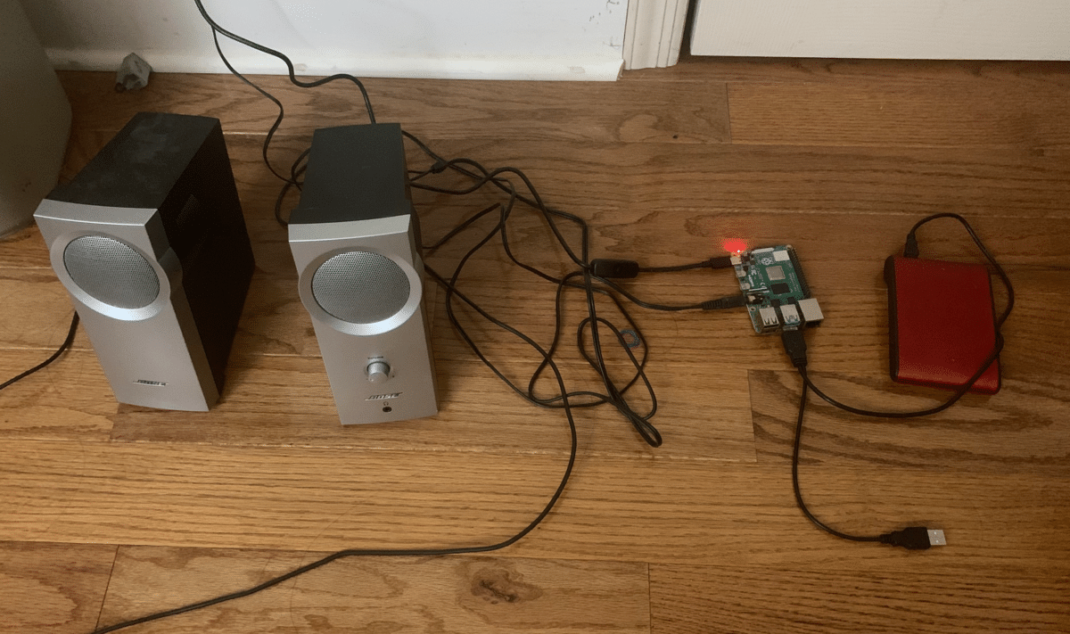 A Raspberry Pi computer attached to an external hard drive and a pair of speakers on the floor.