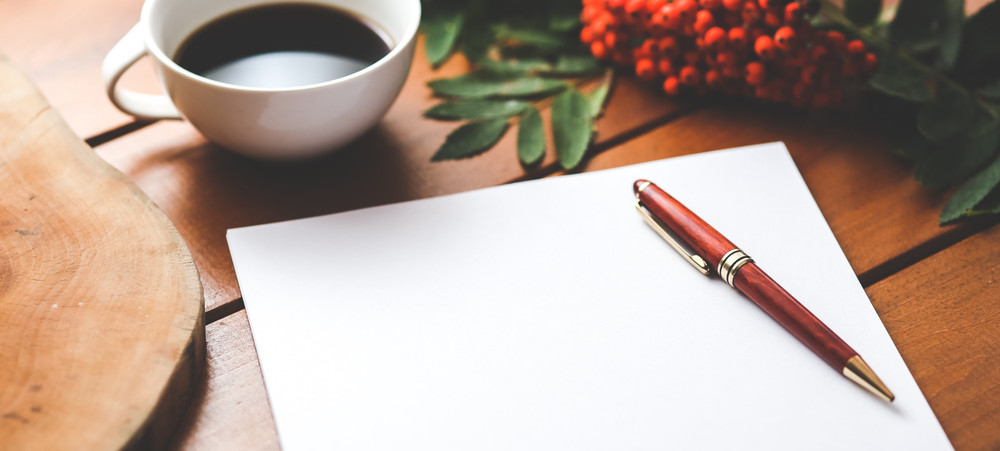 A stylish pen on top of a notebook next to a cup of coffee on a wooden table