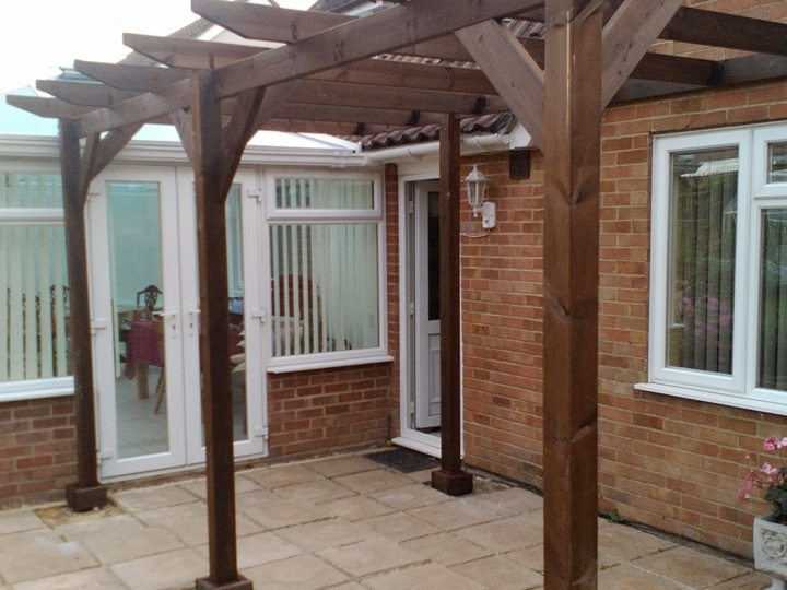 A lean-to pergola built against a customers house, and stained with a dark wood stained