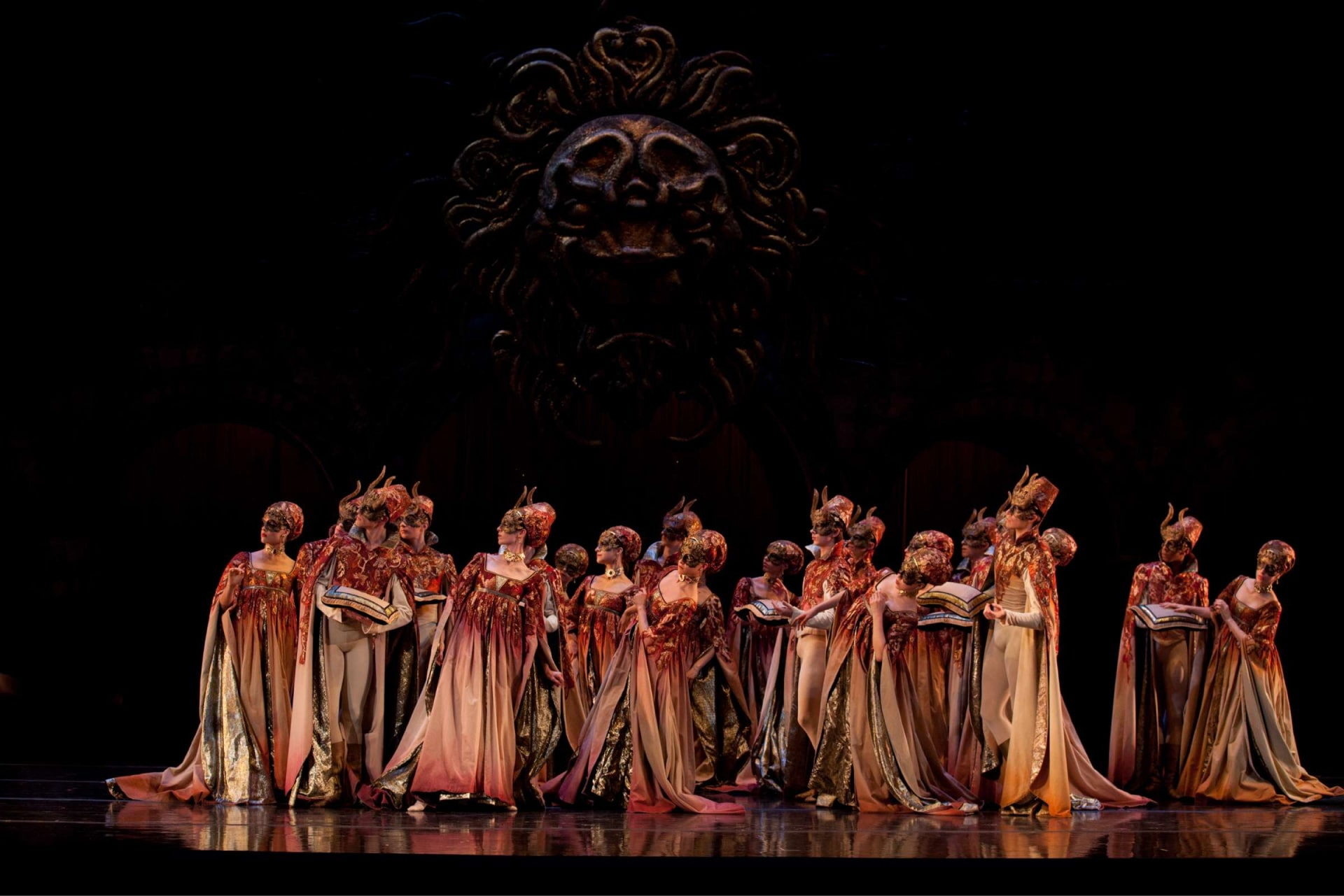 Chorus of dancers in dip-died gowns and masks look left against dark background under giant, lion's head wall ornament.