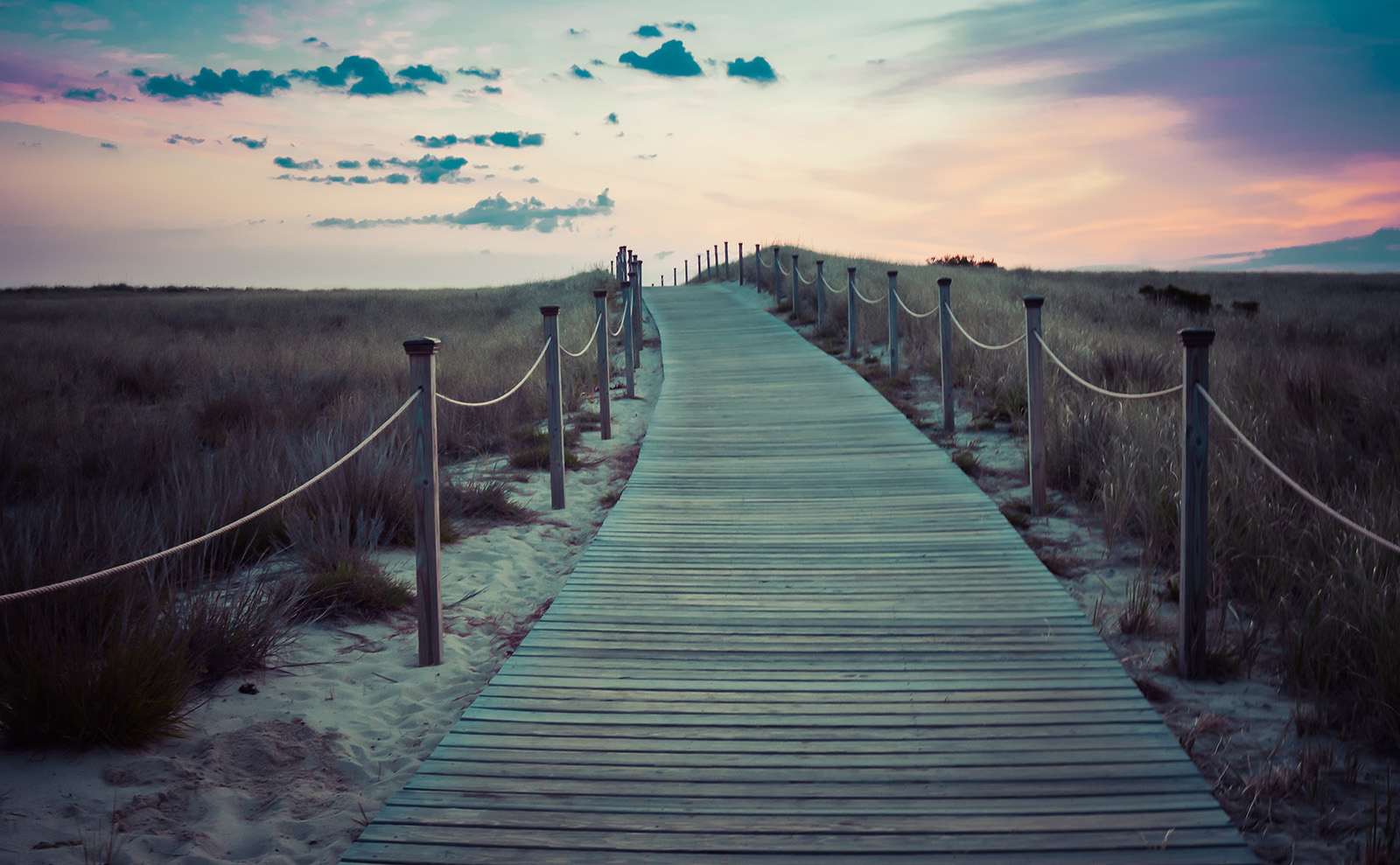 brown wooden boardwalk leading to the beach at sunset