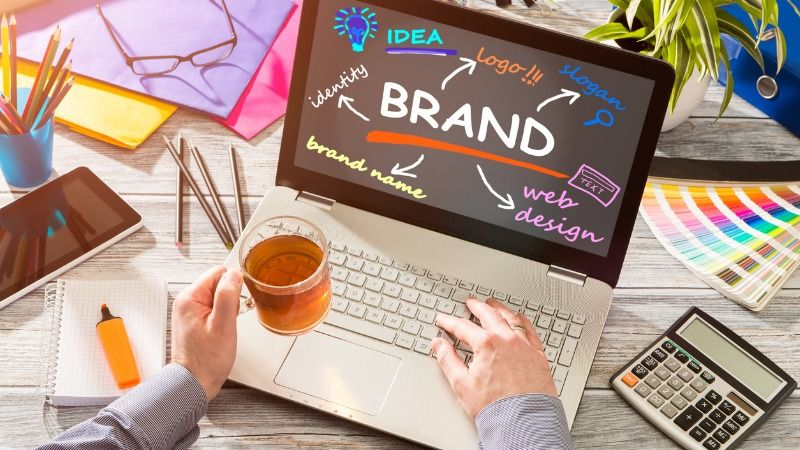 Eine Person, die ein Glas Tee hält, sitzt an einem Tisch mit Stiften, Taschenrechner, Markern, Farbpaletten und einer Brille, vor ihr steht ein Laptop, auf dessen Bildschirm das Wort Marke steht und daneben verschiedene Elemente einer Marke auflistet.