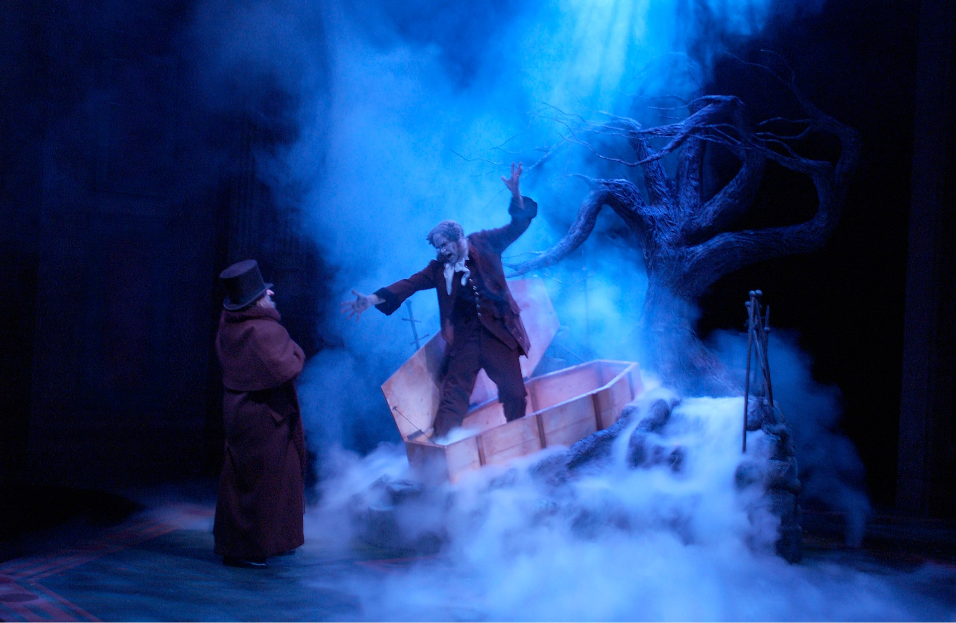 Man in top hat on smoke-filled stage is startled by figure emerging from coffin lit by shafts of cold light.