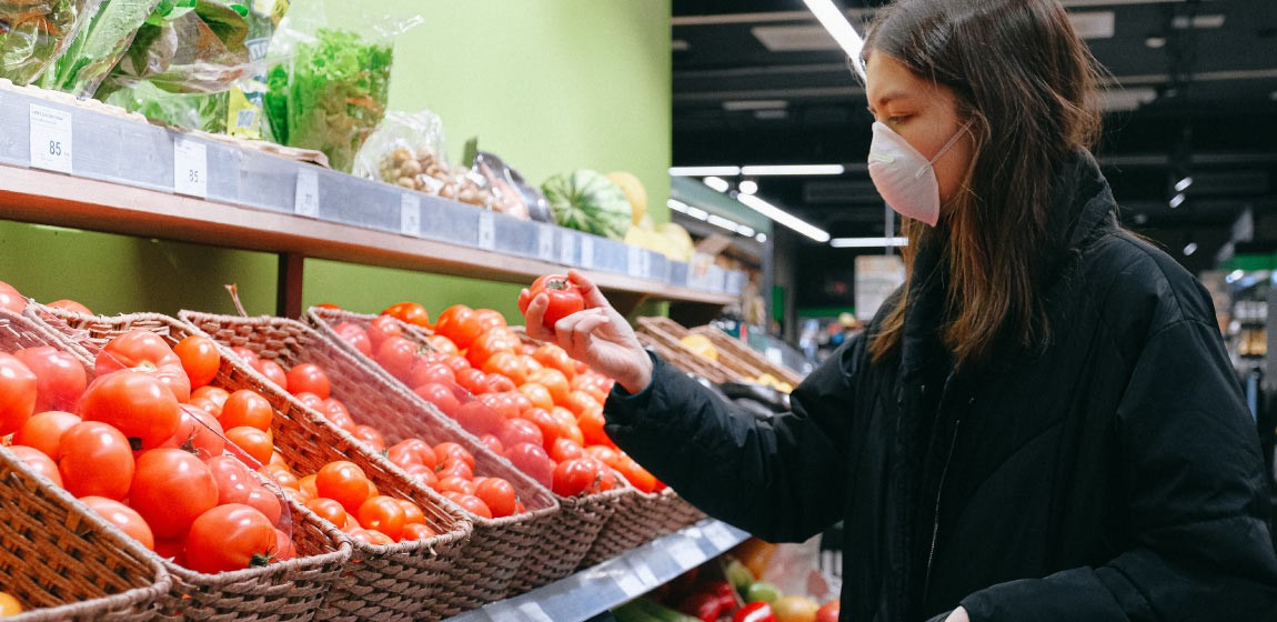 A women looks at tomatoes in a store