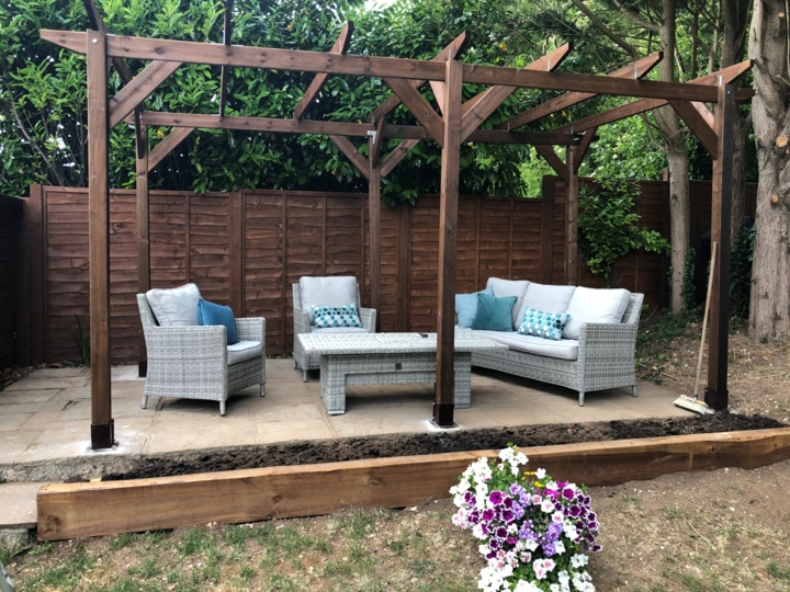 An example of module 5; a double length standalone pergola built on a raised patio, covering some wicker garden furniture