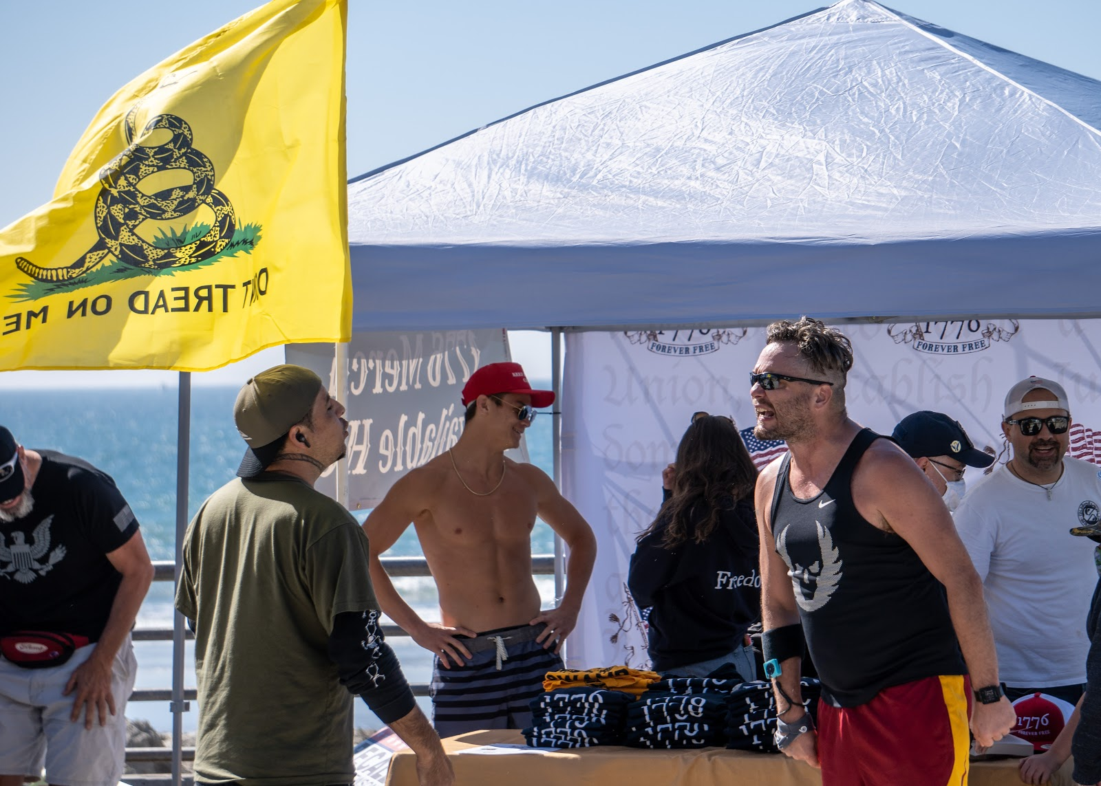 In the foreground there are two men who appear to be shouting aggressively at eachother, neither has a mask on, and the one on the left is wearing a matching olive green hat and t shirt with a long sleeve black shirt underneath. he has a band neck tattoo. the other man is wearing a black tanktop and running shorts, with sunglasses on. behind them there is a dont tread on me flag, and a pop up tent with what appears to be merch, and other maskless people milling about.