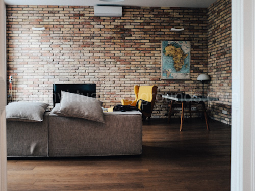 Loft style Home Study Virtual Background for Zoom brick facade and gray sofa
