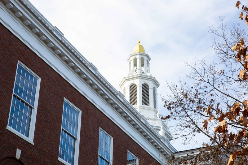 Closeup view of the white and gold spire of Baker Library at Harvard University