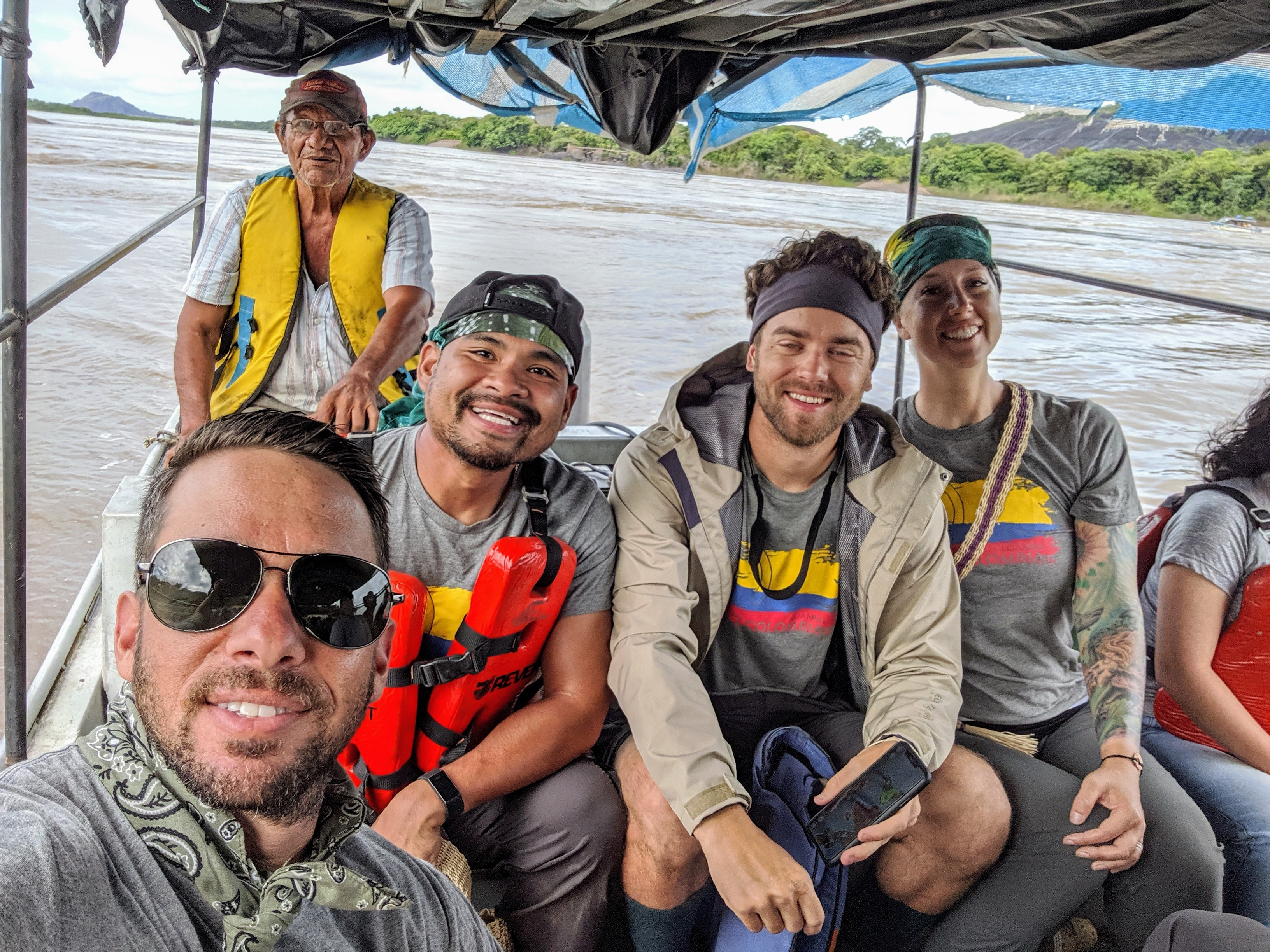 A group of people in a boat, smiling for a picture, on a remote jungle river in colombia,