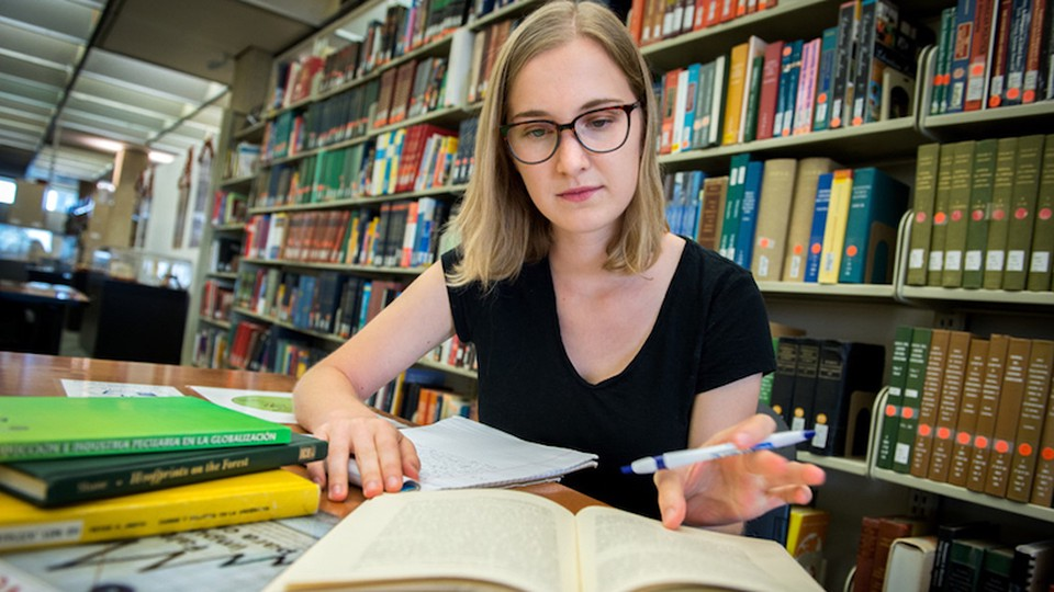 A woman studying at a library.