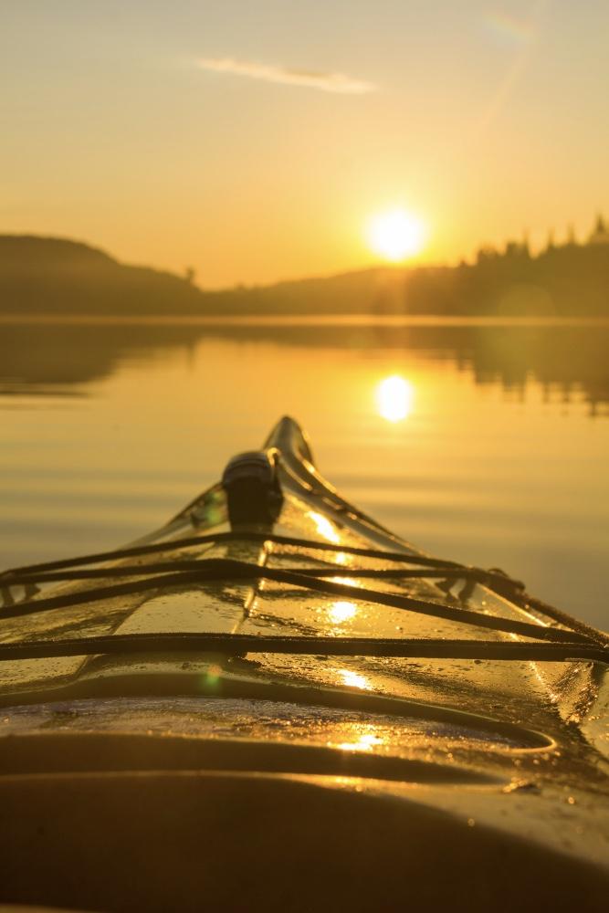 Kayak sur l'eau au lever du soleil