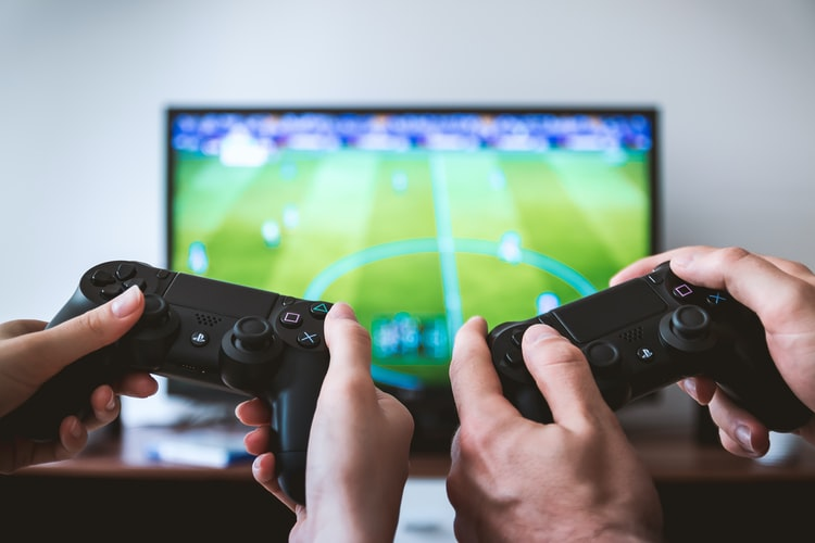 Two people holding video game controllers and playing video game