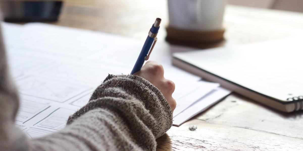 Close-up of a writer's hand, holding a pen and scribbling notes