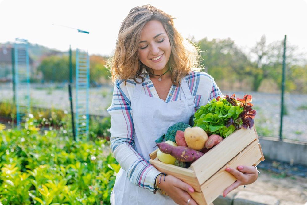 Supply chain - Une jeune femme souriante en tablier, tenant dans ses bras une cagette de légumes sur fond de jardin primeur