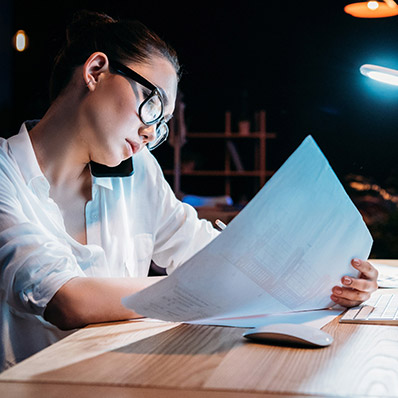 A woman analysing a paper document.