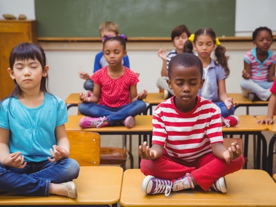 Students sit on desks while meditating.