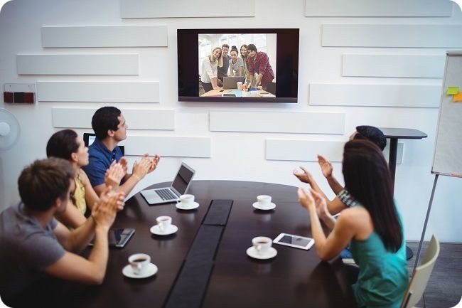 Photo une personne échange avec une autre personne en video conference, son ordinateur portable sur les genoux
