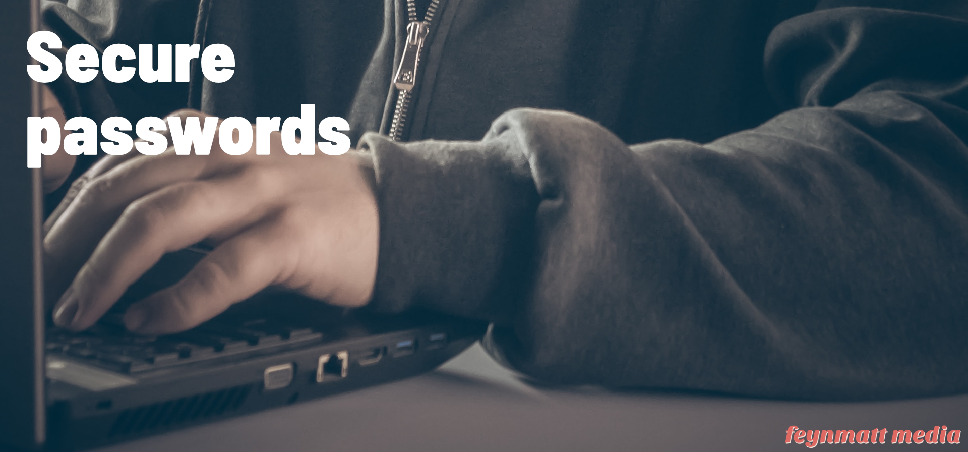 Secure Passwords. Man in black zip hoodie typing on notebook keyboard.