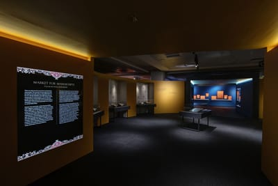A corridor leads into a room. On the corridor's left wall, a lightbox display is titled: 'Market for Manuscripts'. In the room inside, a showcase is in the center, surrounded by other showcases against the walls.