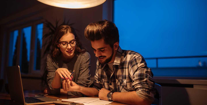 Junges Paar plant am Laptop seine finanzielle Zukunft - Welche Faktoren haben Einfluss auf meine Rente
