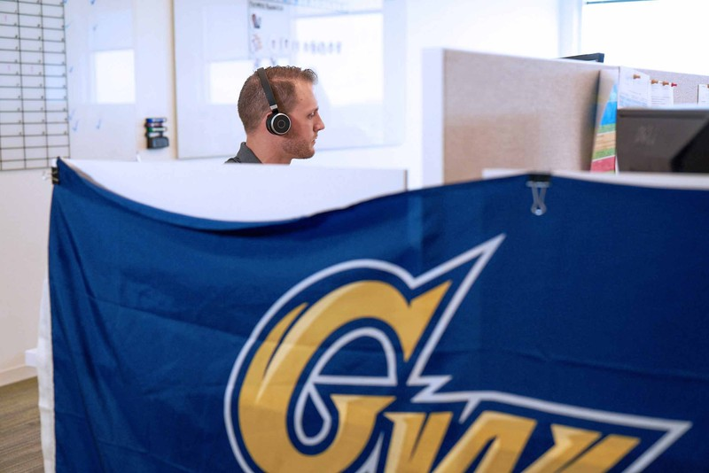 Man sitting in cubicle wearing wireless headphones next to a George Washington University banner