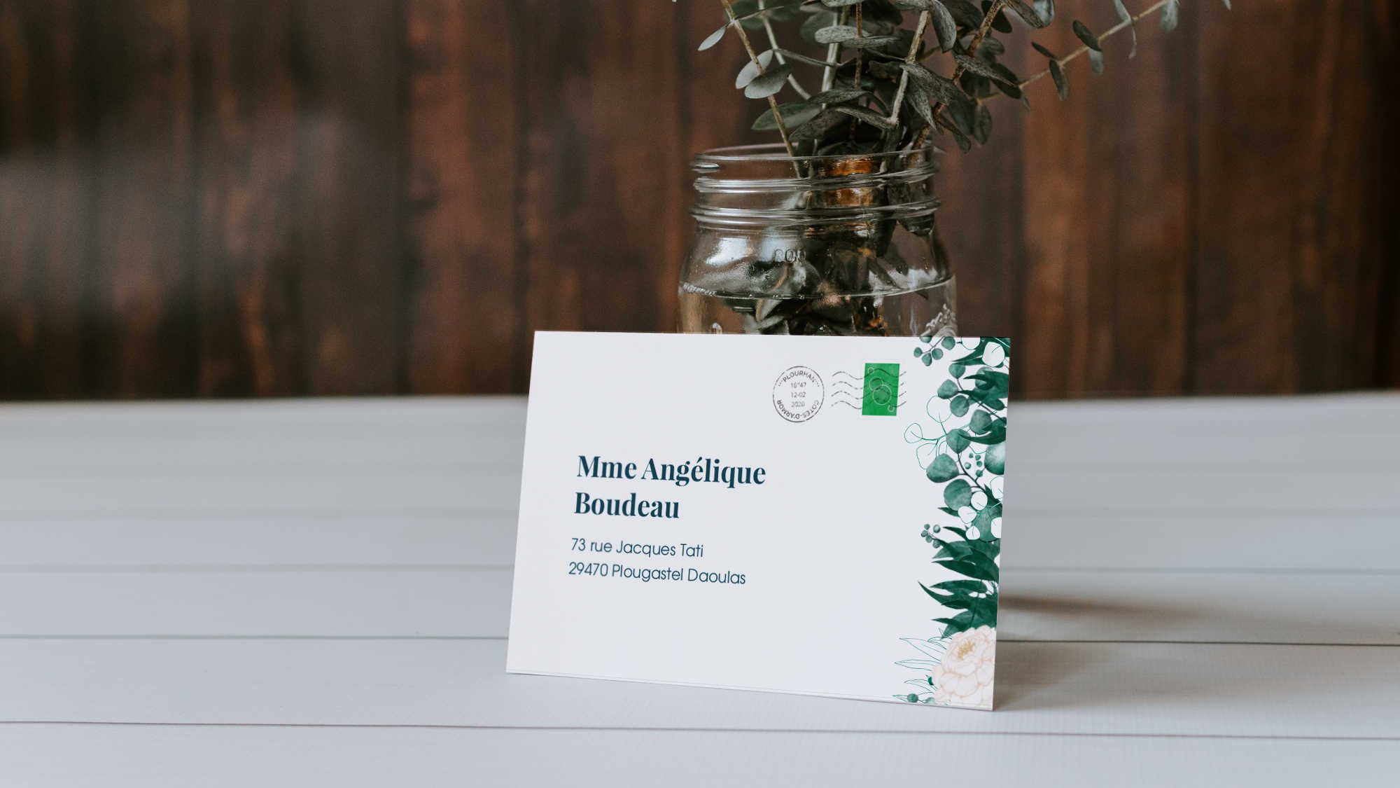 Mockup of the front of the envelope/invitation showing the addressee's name and address, two stamps and plants illustrations. The invite is displayed on the front of a vase containing a green-blue bunch of plants with a wooden panel background visible.