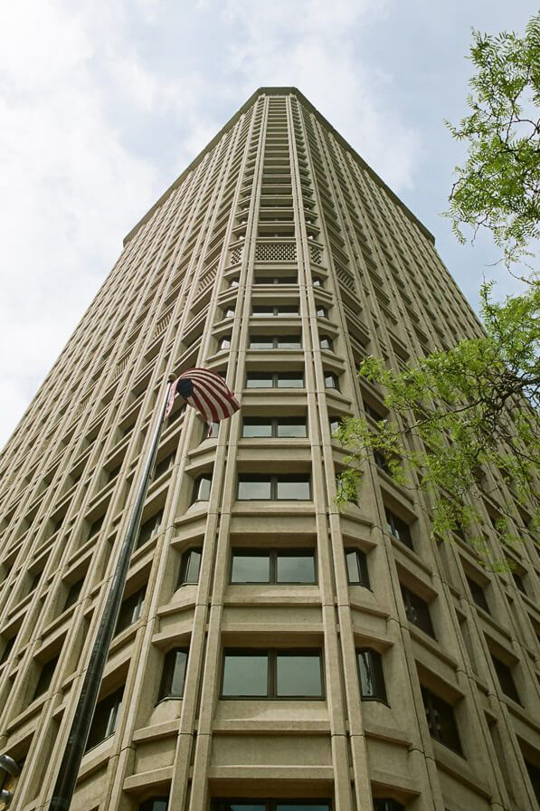 Looking up at the corner of a tall building. In front flies an American flag