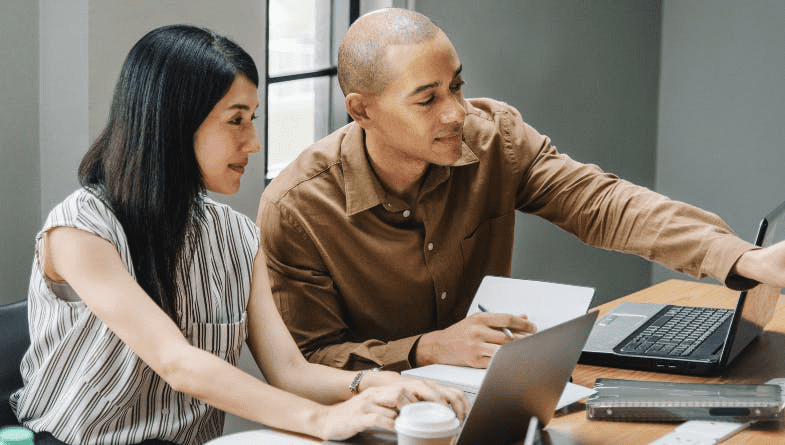 Man leans across table in yellow shirt and points on laptop screen to woman colleague client in grey over books and files to discuss if it's time to move accounting firm into advisory to be advisors #advisory