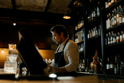 A bartender ringing up a tab at the register.