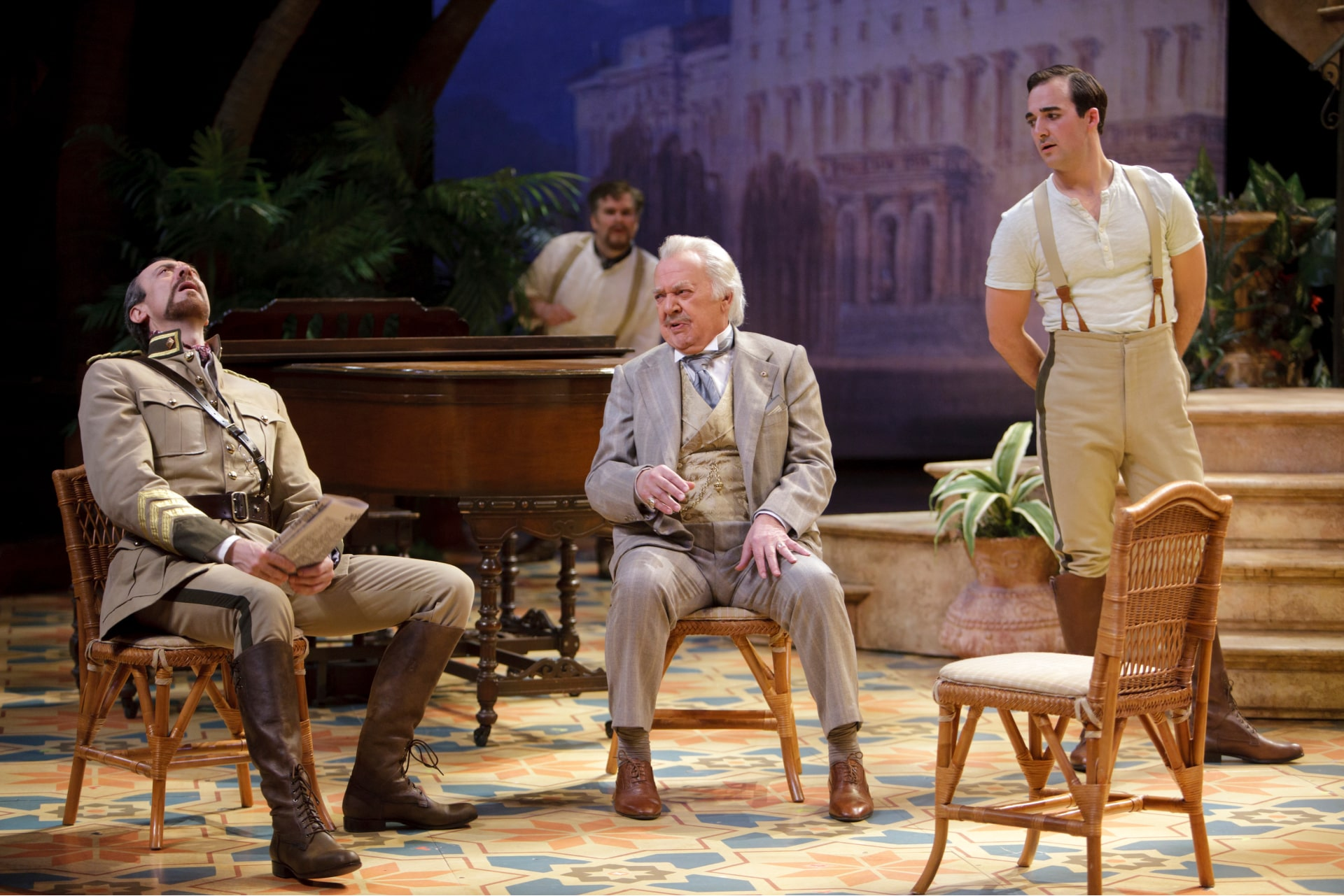 Two men sit on wicker chairs watched by two other men.
