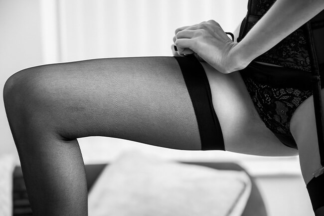A woman adjusting her leg suspenders.