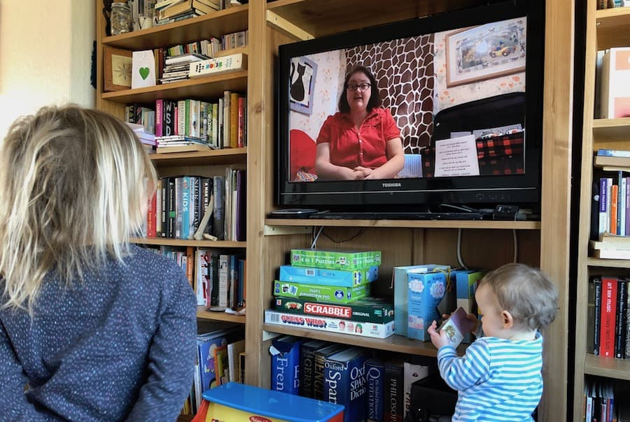 Child watching a woman tell a story on TV.