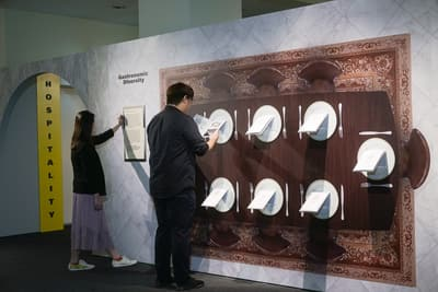 A photo of the Gastronomic Diversity section, with a woman and man browsing it. The wall has a giant dinner table with dinner plates. Informational 'menus' are mounted onto these plates.