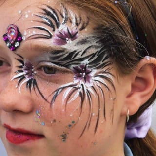 A beautiful floral design and glitter on the left side of a girl's face. Above her nose, some purple-coloured artificial gem-stones are attached with adhesive. Click to view at full size.