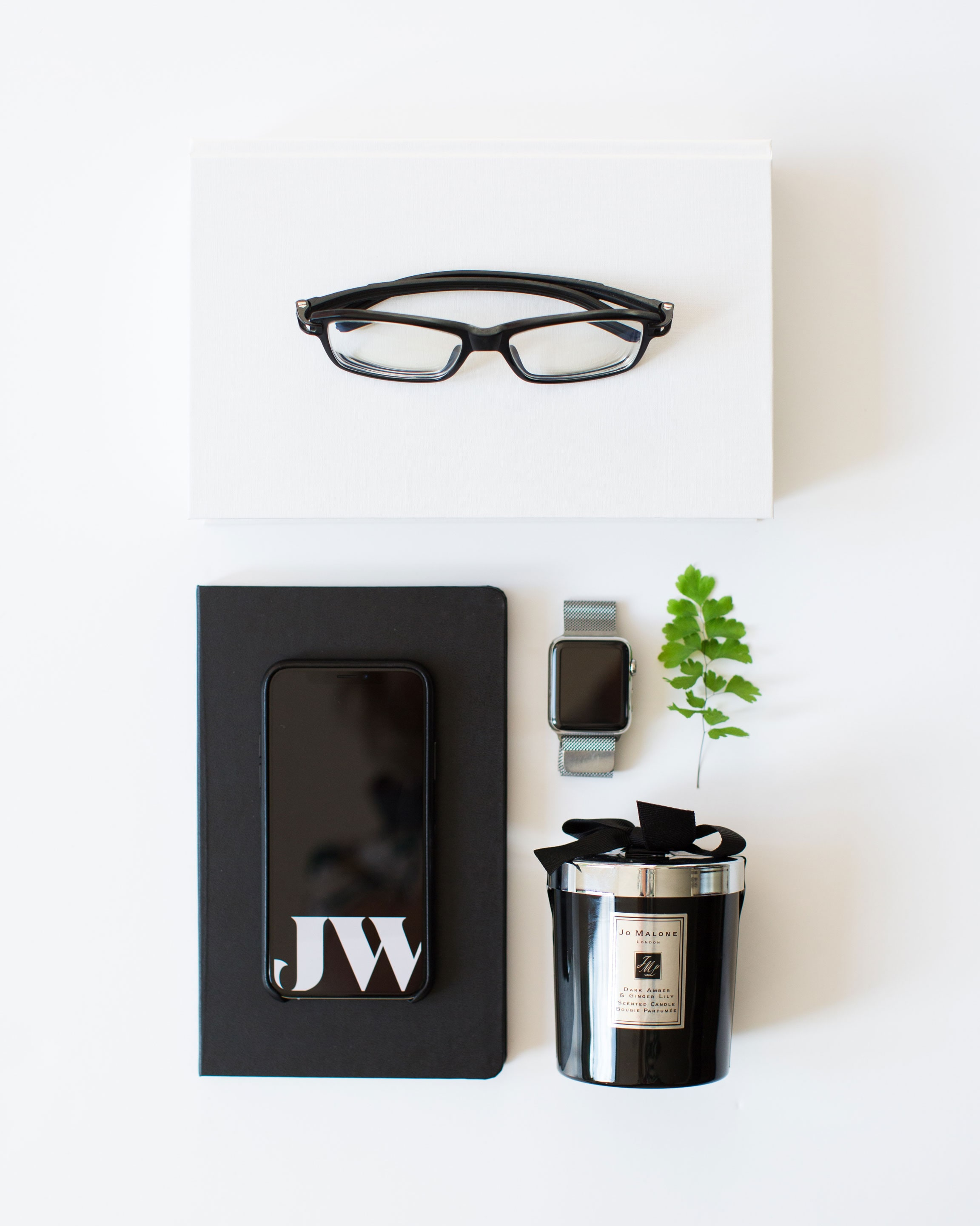 Jack Watkins branding flat lay with iPhone, Jo Malone candle, Moleskine notepad, Apple Watch, glasses and book