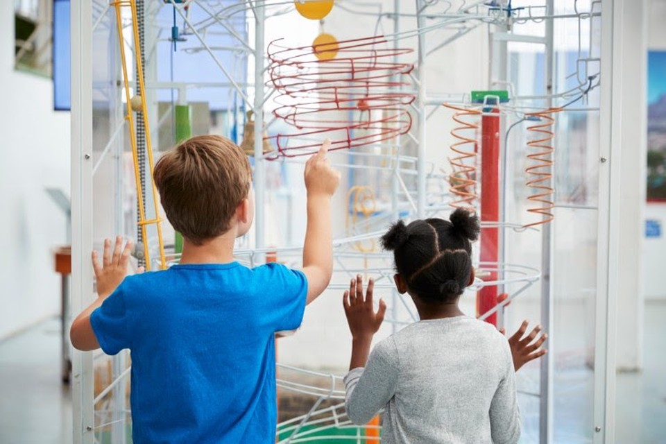 Two children seen from the back interact with a colorful science exhibit at a museum.