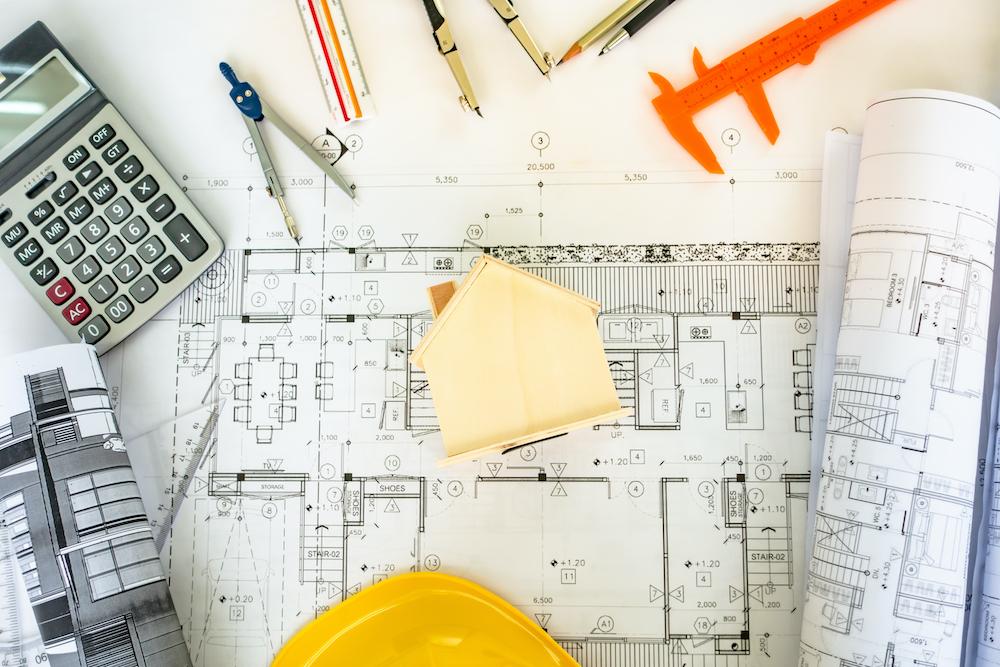 Baupläne mit Werkzeugen und Taschenrechner