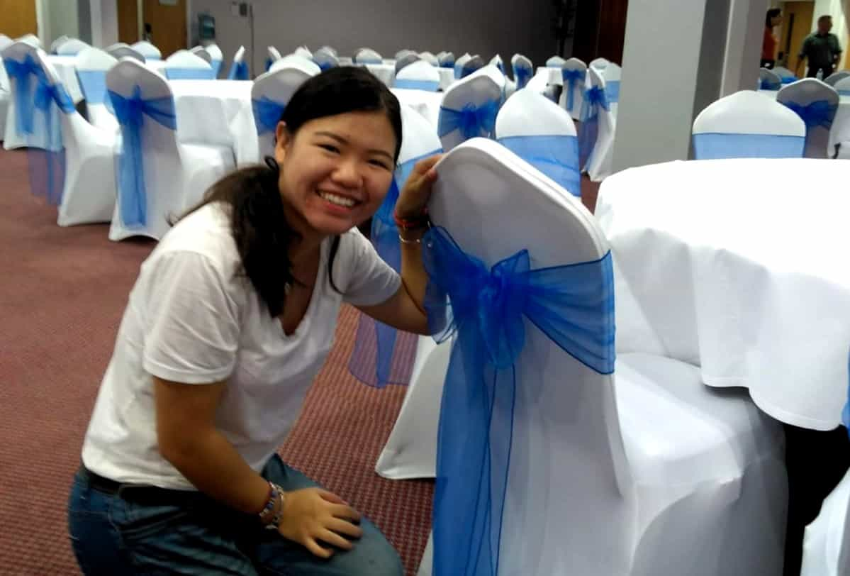Jing smiling putting a blue sash onto a white chair